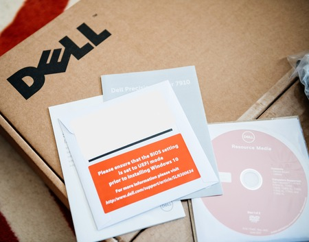 LONDON, UNITED KINGDOM - JUN 15, 2017: Unboxing of new Dell Precision workstation computer box containing multiple Operating System OS DVDs and drivers on CD-drive and Dell logotype and Resource Media 報道画像