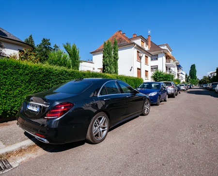 STRASBOURG, FRANCE - JUN 30, 2018: Luxury Black Mercedes Benz AMG S320 4matic parked on a French street in calm neighborhood with beautiful house and clear blue sky Editöryel