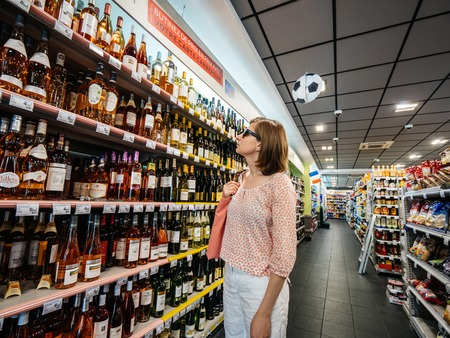 STRASBOURG, FRANCE - JUN 30, 2018: Woman shopping for alcoholic products in French Carrefour Auchan store looking at the shelves with wine, spirits, cognacs and other alcohol