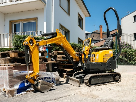 STRASBOURG, FRANCE - JUN 30, 2018: Small yellow excavator tractor rented from Kiloutou in front of the newly constructed apartment building in France