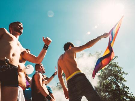 STRASBOURG, FRANCE - JUN 10, 2017: In motion defocused caucasian excited gay men people dancing waving rainbow flag at Lesbian Gay Bisexual Transgender LGBT visibility march pride Festigays