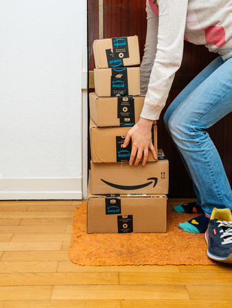 PARIS, FRANCE - JAN 13, 2018: Multiple Amazon Prime packages delivered to a home door woman trying to lift heavy boxes - preparing to do the unboxing Editorial