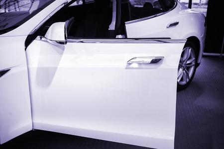 PARIS, FRANCE - NOV 29, 2014: New white Tesla Model S electric car detail open driver door - blue color cast