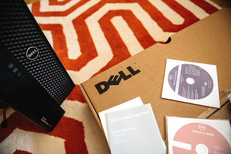 LONDON, UNITED KINGDOM - JUN 15, 2017: Dell Precision T7910 workstation computer box unboxing containing Operating System OS DVDs and drivers on CD-drive during unboxing