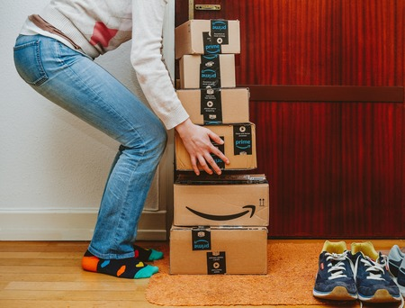 PARIS, FRANCE - JAN 13, 2018: Woman lifting heavy stack of Amazon Prime packages delivered to a home door Редакционное