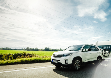 MUNCHEN, GERMANY - OCT 7, 2018: Fast driving on German autobahn Kia Niro Hybride Rechargeable car with RV recreational vehicle trailer - beautiful sunlight flare Redakční