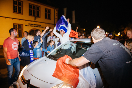 STRASBOURG, FRANCE - JULY 10, 2018: Man waving France flag from car Unique French celebration after the victory of France qualify for the final of the 2018 FIFA World Cup after their victory