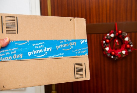 PARIS, FRANCE - JUL 12, 2108: Hand holding next to door Amazon Prime Day cardboard parcel with special blue scotch tape for the Prime Day offering a day of deals, discounts, and unabashed shopping