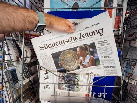 PARIS, FRANCE - 16 JUILLET 2018 : l'achat d'un journal annonçant le titre de tennis d'Angélique Kerber à Wimbledon