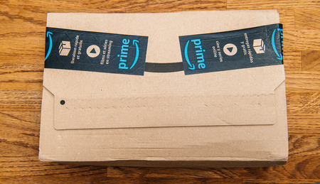 PARIS, FRANCE - JUL 12, 2018: Amazon Prime cardboard parcel box with tape for the Prime membership offering a day of deals, discounts, and unabashed shopping