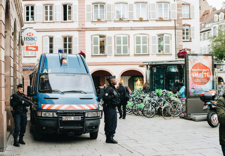 STRASBOURG, FRANCE - OCT 28, 2017: Armed police officers near blue van surveilling central Place gutenberg square near HSBC bank branch during anti-terrorist national plan