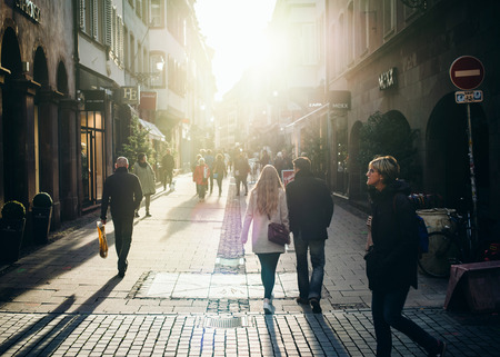 STRASBOURG, FRANCE - OCT 28, 2017: Majestic sunlight over large crowd and long shadows of people on the pedestrian French street Rue des Juifs of shops and restaurants