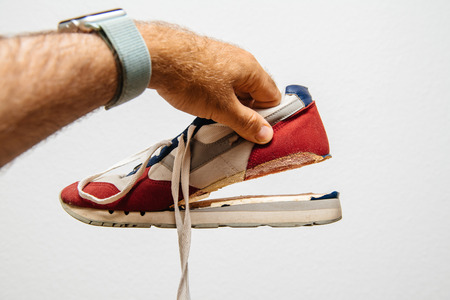 Man holding against white background one sport footwear sneaker with broken sole - quality manufacturing problems Stockfoto