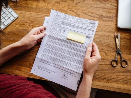 Paris, Frankrijk - Jul 1, 2018: Vrouw leest brief uitgegeven door Spaanse autoriteiten van de Direcion General de Trafico met verkeersboete voor het passeren van de maximumsnelheid Redactioneel