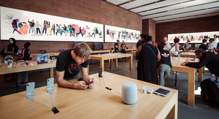 PARIS, FRANCE - JUL 16, 2018: Modern Apple Mac store main hall with customers playing with latest iPhone X smartphone and HomePod speaker on table