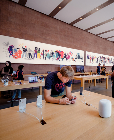 PARIS, FRANCE - JUL 16, 2018: Modern Apple Mac store main hall with handsome man admiring playing with latest iPhone X smartphone next to HomePod speaker Editorial