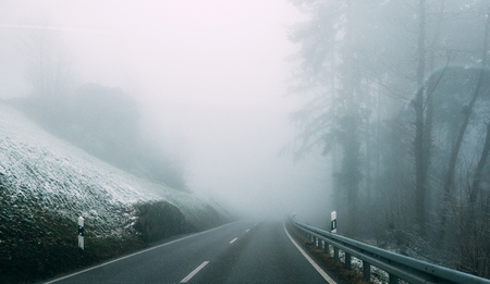 Landscape of lonely paved road running away among slope in slight snow and coniferous trees in thick fog