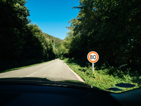 New French 80kmph speed limit sing seen on a public road in the forest.