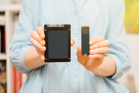 Woman hands holding new hard drive disk with high read and write speed comparing to SSD solid state drive Standard-Bild