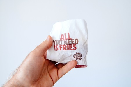 PARIS, FRANCE - JUNE 5, 2018: Burger King paper bag with all you need is fries and Burger King logotype in man hand against white bakground. Burger King is a global chain of hamburger fast food restaurants headquartered in United States.