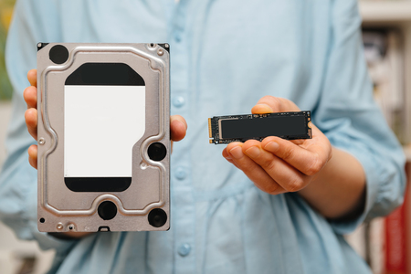 Woman hands holding new NVME PCIE SSD hard drive disk with high read and write speed with bigh old HDD drive