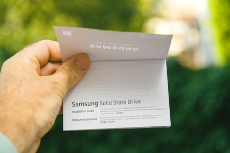 PARIS, FRANCE - AUG 3, 2018: Man hand holding packaging instruciton of NVME PCIE SSD hard drive disk with high read and write speed Samsung 870 Pro Installation guide and warranty statement Editorial