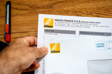 PARIS, FRANCE - Aug 8, 2018:  Man holding on office table a letter and invoice from Nikon Corporation for the camera equipment