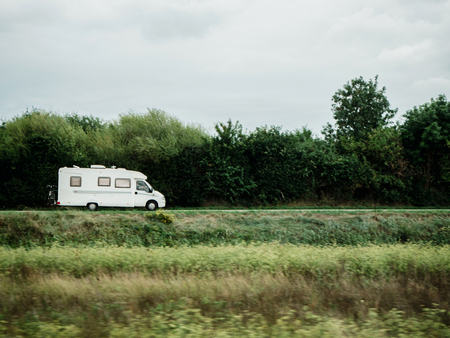 White motorhome RV Camping van driving fast - camper van driving in green clean ecological environment to the camping recreation time Stock Photo - 107129208