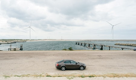 Vrouwenpolder, Netherlands - Aug 25, 2018: Luxury Skoda car parked in the bay - elevated view - rainy cloudy netherlands weather and big wind turbines for the elctric hybrid car Editorial