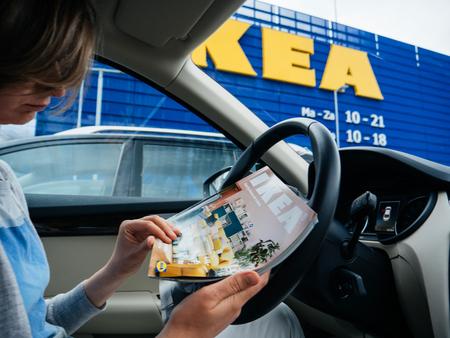DELFT, NEDERLAND - 23 Aug 2018: Elegante vrouw die IKEA meubelmagazine-catalogus leest in de auto geparkeerd op de brede IKEA-parkeerplaats in de hoofdwinkel in Nederland, hoofdkantoor van IKEA Global