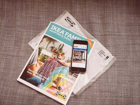 PARIS, FRANCE - MAY 3, 2017: IKEA Family Shopping and Ideas monthly catalogue sent by post and IKEA website opened on the smartphone telephone for order online new products
