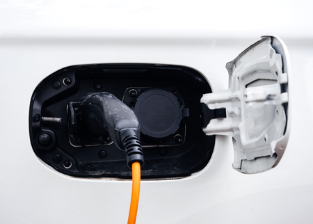Yellow and black cable of electric car charger being plugged in at the parking - modern ecological clean environment car