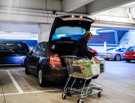 Side view of woman with shopping trolley near car putting bags with groceries into trunk on parking lot Archivio Fotografico