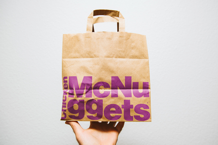 PARIS, FRANCE - AUG 29, 2018: Crop hand showing brown paper from McDonalds with McNuggets bag with shop advertisement on side against white background
