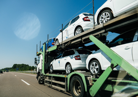 View of lgeneric white long truck trailer transporting new cars and riding on highway in sunlight under blue sky