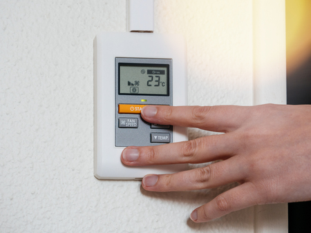 Woman hand adjusting a wall mounted temperature for the room AC air conditioning system sunlight flare
