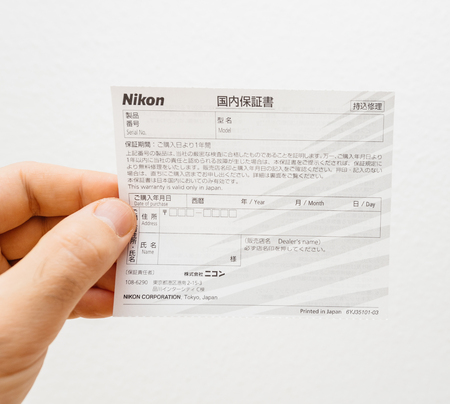 PARIS, FRANCE - FEB 5, 2018: Man holding certificate of warranty of a Nikon DSLR camera accessory in Japanese language against white background