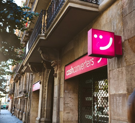 BARCELONA, SPAIN - OCT 11, 2017: Exterior shot of pink sign with smile hanging above cash converting retail on street Cahs Converters, sign,  on wall