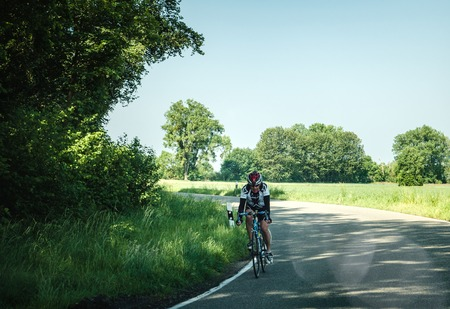 KARLSRUHE, GERMANY - MAY 18, 2018: Man in helmet and sportswear riding bicycle on empty paved road in countryside in summertime