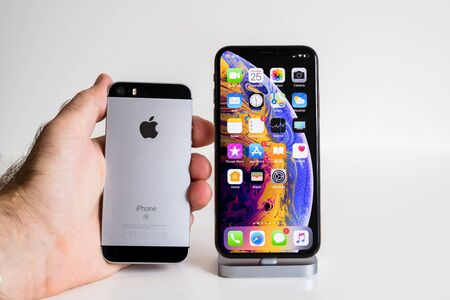 PARIS, FRANCE - SEP 25, 2018: Male hand compare new iPhone Xs and Xs Max smartphone model by Apple Computers close up with older iPhone Se Publikacyjne