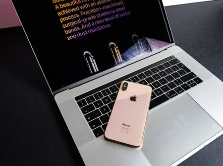 PARIS, FRANCE - SEP 25, 2018: New iPhone Xs and Xs Max smartphone model by Apple Computers close up of the newest golden Apple Iphone device on MacBook pro keyboard Publikacyjne