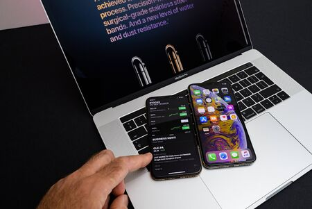 PARIS, FRANCE - SEP 25, 2018: New iPhone Xs and Xs Max smartphones model by Apple Computers close up photo on the keyboard of Apple MacBook pro laptop 15 inch hand testing stocks app