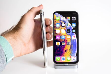 PARIS, FRANCE - SEP 25, 2018: Male hand compare new iPhone Xs and Xs Max smartphone model by Apple Computers close up with man showing thickness of steel phone Publikacyjne