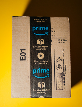 PARIS, FRANCE - SEP 28, 2018: PaArcel delivery Amazon Cardboard box against yellow background with seal scotch tape featuring prime video and one day delivery