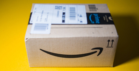 PARIS, FRANCE - SEP 28, 2018: Front view of new Amazon Cardboard box against yellow background smile - tilt-shift lens
