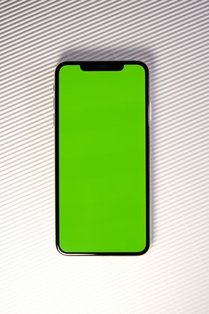 PARIS, FRANCE - SEP 27, 2018: Detail of new Apple Computers iPhone Xs Max as hero object on white background - smartphone telephone with OLED display with green chroma key screen on stripe background Reklamní fotografie - 110496782
