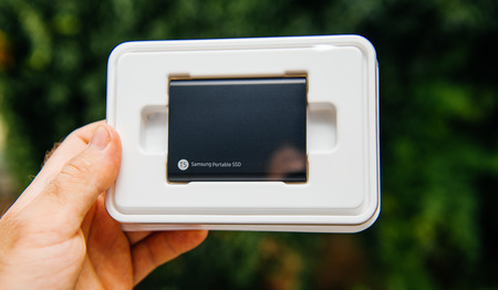 PARIS, FRANCE - AUG 14, 2018: Man hand holding protection plastic box of Samsung T5 Portable SSD 2 tb external hard drive disk with high read and write speed against green background unboxing testing