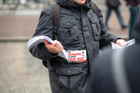STRASBOURG, FRANCE - MAR 22, 2018: People gathering in Place Kleber square during CGT General Confederation of Labour demonstration protest against Macron French government string of reforms - man distributing flyers manifests