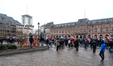 STRASBOURG, FRANCE - MAR 22, 2018: People gathering in Place Kleber square during CGT General Confederation of Labour demonstration protest against Macron French government string of reforms rainy weather in front of Aubette building