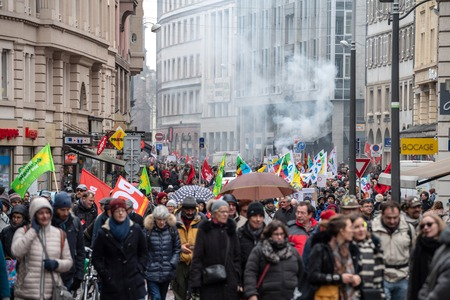 STRASBOURG, FRANCE - MAR 22, 2018: Smoke grenade in background of crowd as CGT General Confederation of Labour workers with placard at demonstration protest against Macron French government string of reforms